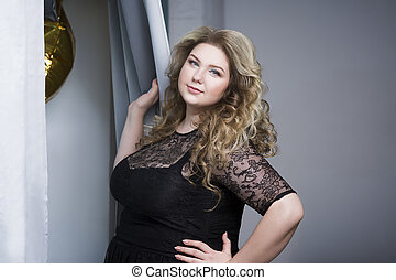 Blonde plus size model in black dres, woman portrait on gray background