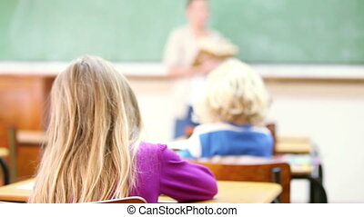 Blonde pupil smiling in the classroom