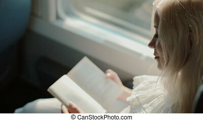 Blonde reading a book in the train