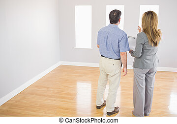 Blonde realtor showing a room to a potential buyer - Blonde...