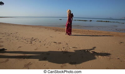 blonde sad girl in bright dress walks along beach