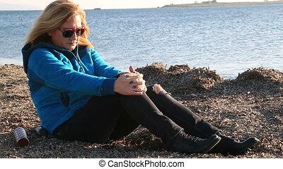 Blonde sad woman sitting at the seaside