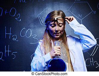 Blonde scientist looking at chemistry liquid