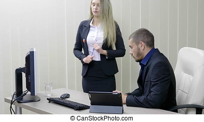 Blonde Secretary and her boss at the table next to a computer