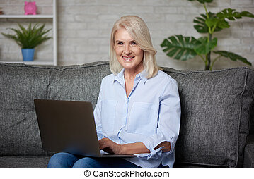 blonde senior woman is working with laptop at home