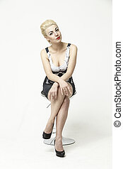 blonde sits on a chair in the studio