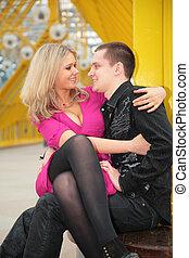 blonde sits on boy`s knees on yellow footbridge