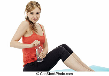 blonde sitting fitness woman opening a bottle of water on white background