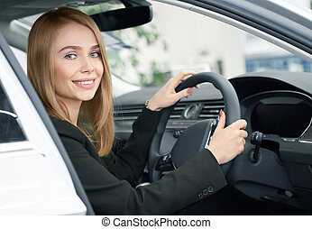 Blonde sitting in new automobile, buyer of car.