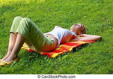 Blonde sleeping in meadow