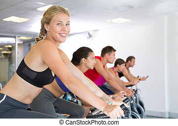 Blonde smiling at camera during spin class at the gym