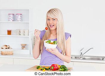 Blonde smiling female eating her salad