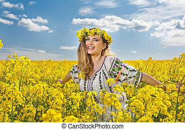 Blonde smiling in canola field - Young girl wearing Romanian...