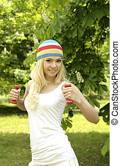 Blonde smiling sporty girl working out outdoor.