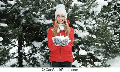 Blonde smiling woman throws snow in winter pine forest outside