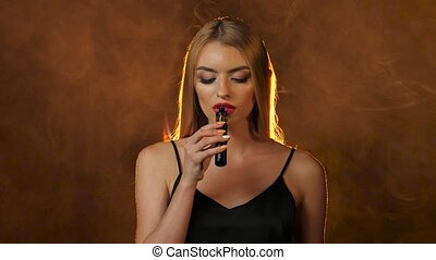 Blonde smokes an electronic cigarette, she's sexy. Golden...