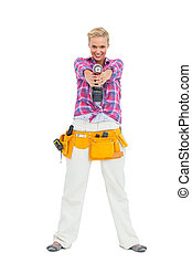 Blonde standing while pointing a drill at camera