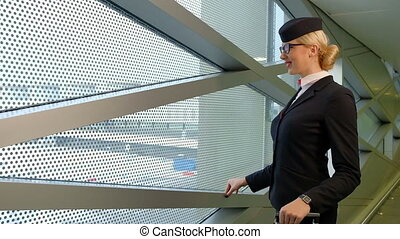 Blonde stewardess standing in waiting room before flight indoors