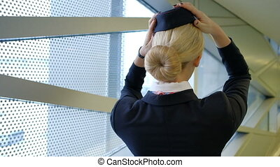 Blonde stewardess standing in waiting room wearing hat uniform