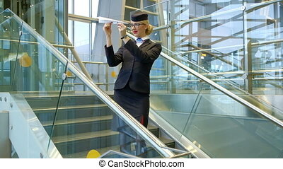 Blonde stewardess standing on stairs making toy paper plane in hall
