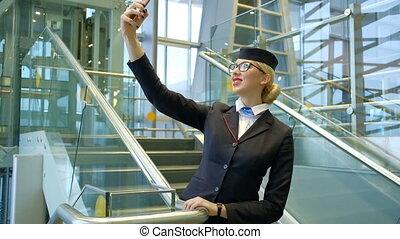 Blonde stewardess standing on stairs making selfie on smartphone
