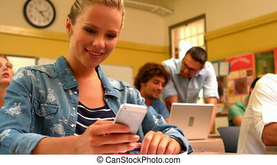 Blonde student texting on her phone