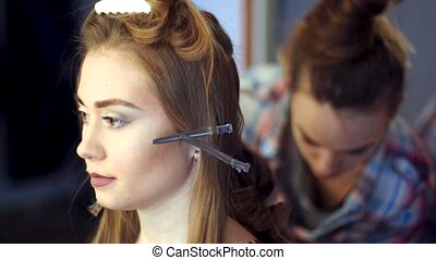 blonde stylist girl makes hairstyle to a young woman