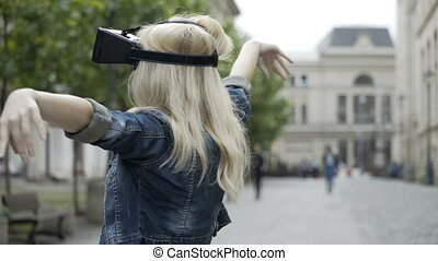 Blonde teen girl dancing ballet using virtual reality googles