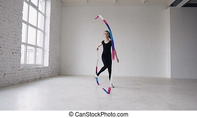 Blonde teenage girl dance rhythmic gymnastics, modern with colored ribbon in black body in the white background at sport school
