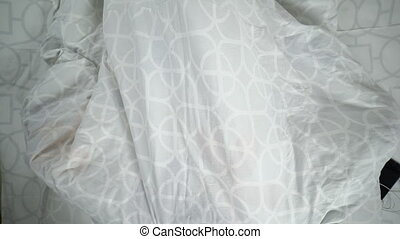 Blonde teenage girl lying in bed under blanket hiding her face with a smile
