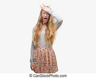 Blonde teenager woman wearing flowers skirt surprised with...