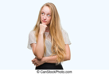 Blonde teenager woman wearing moles shirt with hand on chin thinking about question, pensive expression. Smiling with thoughtful face. Doubt concept.