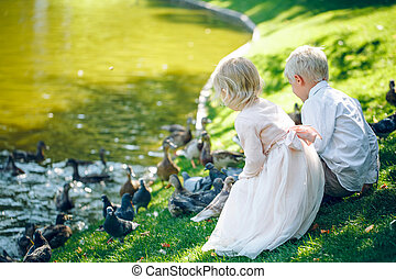 Toddlers boy and girl sitting on grass near the lake and fed the pigeons with bread
