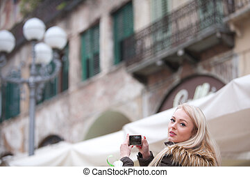 blonde tourist taking photographs in the city