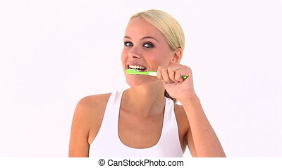 Blonde using a toothbrush