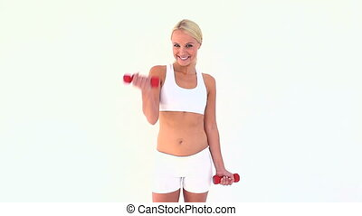 Blonde using dumbbells against white background