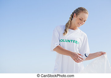 Blonde volunteer picking up trash on the beach on a sunny ...