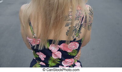 Blonde walks away from the camera in the parking lot -...
