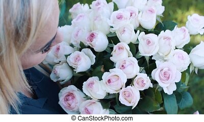 Blonde with a bouquet of roses in the garden