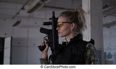 Blonde with arms in the building - A woman plays airsoft,...
