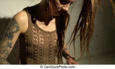Blonde with dreadlocks playing tapidrum video - Tattooed ...