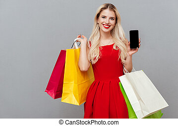 Blonde with phone and bags