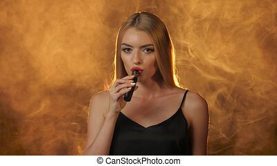 Blonde with red lips smokes an electronic cigarette and smiles. Golden smoke background