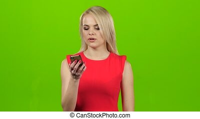 Blonde with smile talking on mobile phone on green screen,...