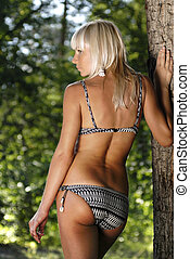 blonde woman amongst trees - beautiful back of woman in...