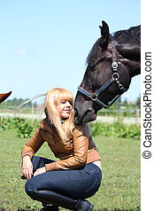 Blonde woman and black horse portrait in summer