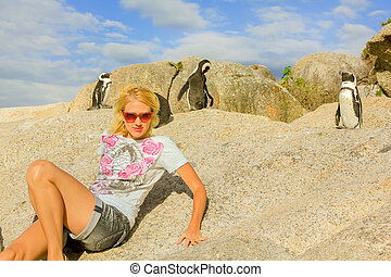 blonde woman sitting on the rock of Boulder Beach in summer, popular for an African penguins colony. Cape Town in Western Cape, South Africa.