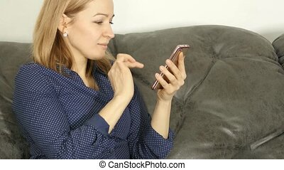 blonde woman at home sitting on a sofa and using smartphone