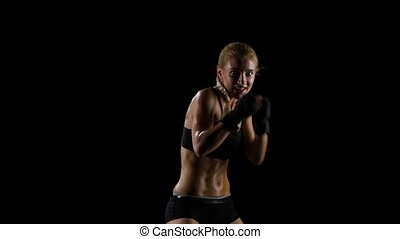 Blonde woman boxer the smiling makes the blows