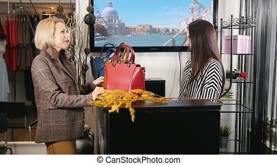 Blonde woman buying dress in clothes store